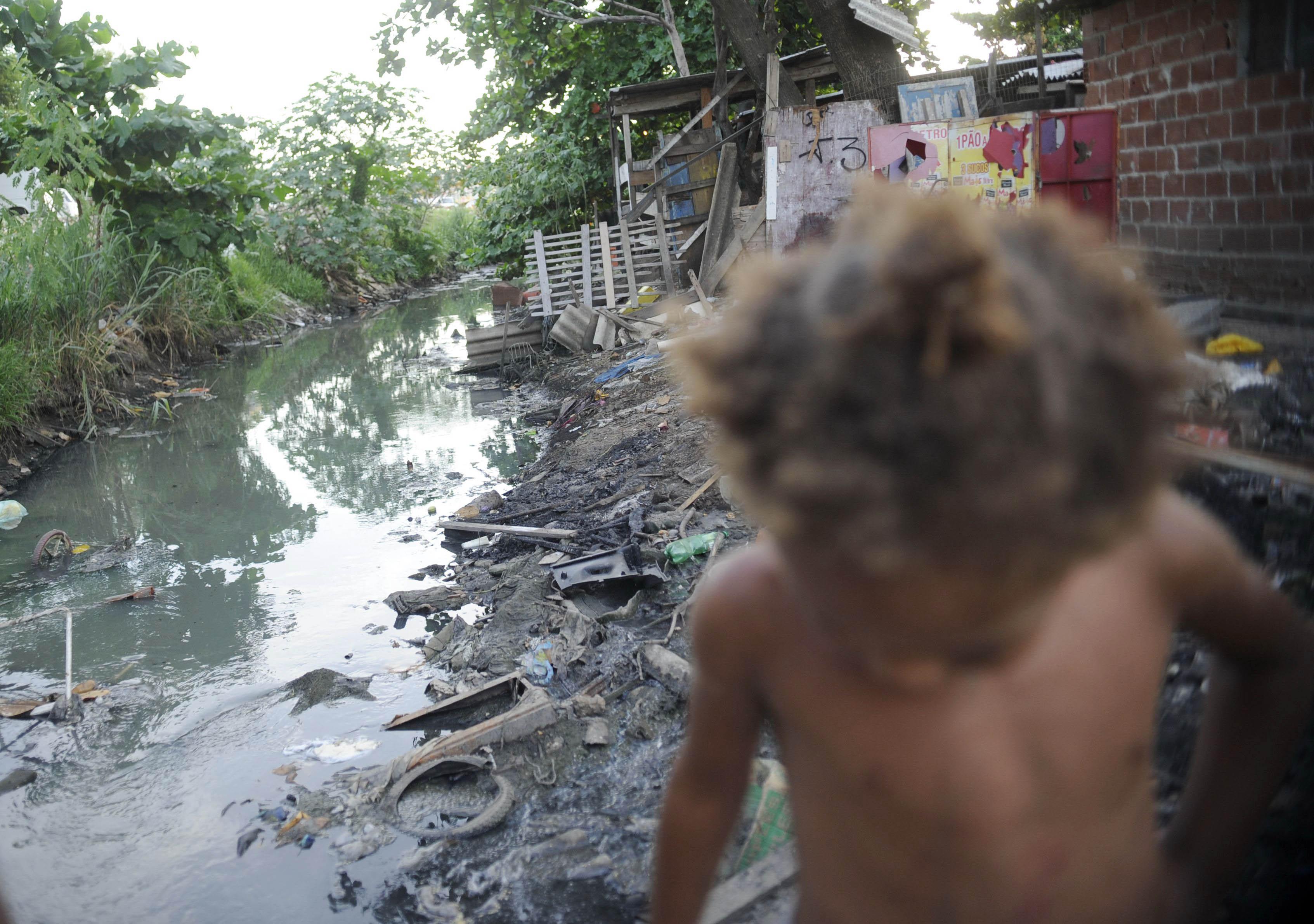 Criança caminha ao lado de um córrego poluído no Complexo da Maré, no Rio de Janeiro (Fernando Frazão/Agência Brasil/via Fotos Públicas)