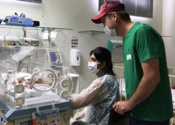 Daiane e o marido ao lado de Ayla Vitória na Unidade de Terapia Intensiva Infantil (Unimed Catanduva/Divulgação)