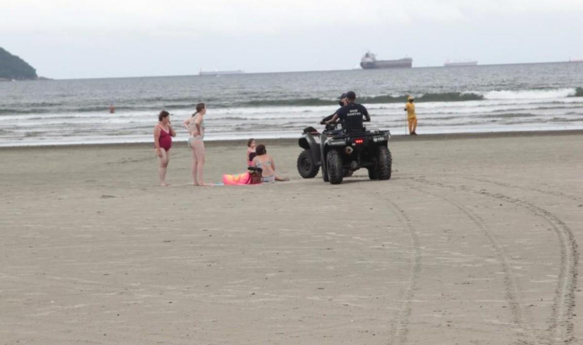Guarda Municipal orienta banhistas sobre proibição de ficar sentado na areia (Pref. de Santos)